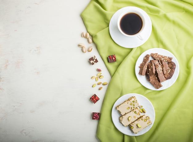 Tradycyjne arabskie słodycze chałwa sezamowa z czekoladą i pistacjami oraz filiżanką kawy. widok z góry