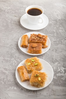 Tradycyjne arabskie słodycze na białym talerzu i filiżankę kawy. widok z boku.