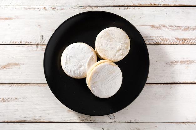 Tradycyjne argentyńskie alfajores z dulce de leche i cukrem na białym drewnianym stole