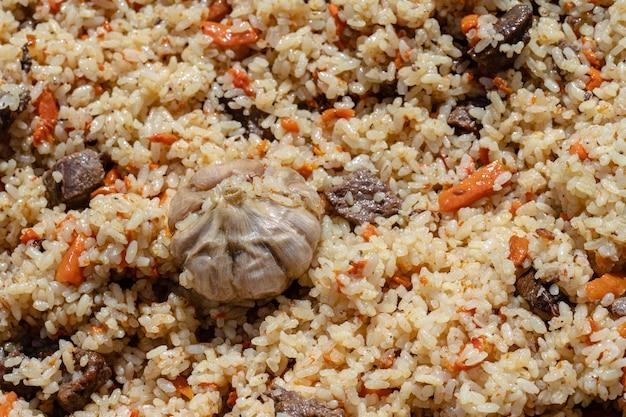 Tradycyjne azjatyckie danie kulinarne - pilaw. składniki: ryż z plastrami mięsa, tłuszczu i warzyw (marchew, czosnek), przyprawy – popularny przepis. zbliżenie na tle wschodniej smaczne jedzenie.