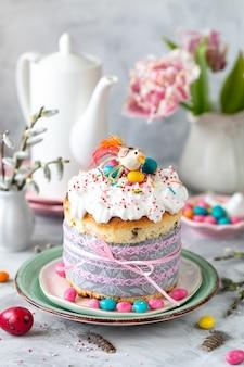 Tradycyjne babeczki wielkanocne ciasto. ciasto wielkanocne, kolorowe jajka i wiosenne kwiaty. pionowy