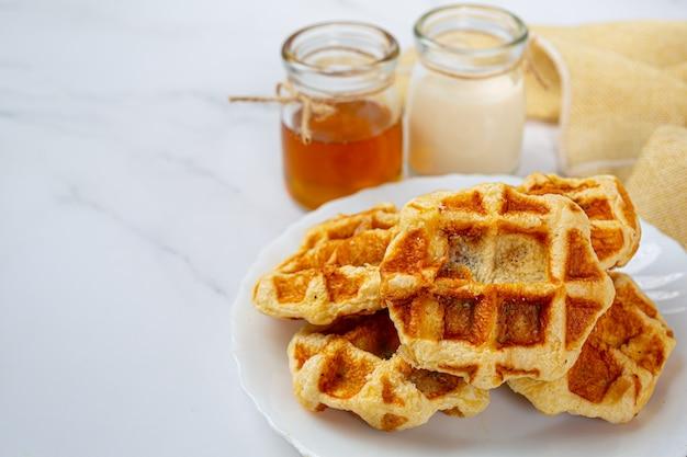 Tradycyjne belgijskie gofry, sos z pomarańczy i jagód oraz filiżanka kawy na słodkie śniadanie, kompozycja na jasnym tle.