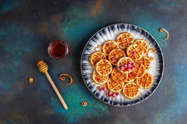 Tradycyjne belgijskie gofry z miodem i mrożonymi jagodami.