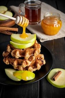 Tradycyjne belgijskie gofry zwieńczone pokrojonym zielonym jabłkiem i miodem spływającym z patyczka oraz filiżanką herbaty. skład śniadania na ciemnej powierzchni drewnianej.