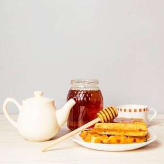 Tradycyjne belgijskie miękkie świeże gofry z miodem i czajnikiem na stole