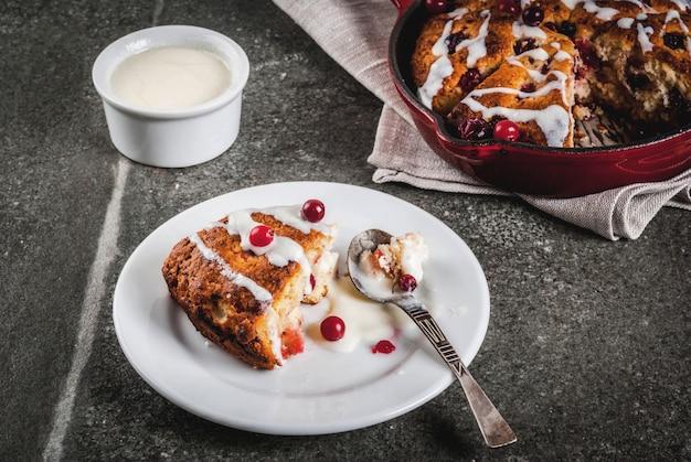 Tradycyjne brytyjskie angielskie wypieki. ciastka żurawinowe bułeczki z skórką pomarańczową, ze słodką białą polewą
