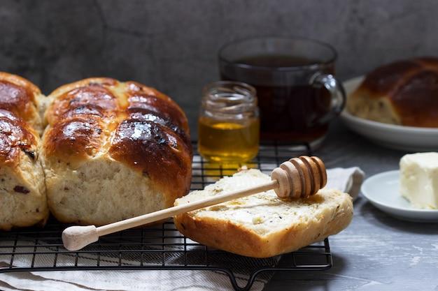 Tradycyjne bułeczki na gorąco z miodem i masłem na betonowej powierzchni