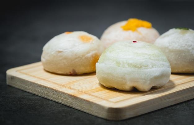 Tradycyjne chińskie ciasto na drewnianym talerzu na ciemnym tle dla koncepcji żywności i piekarni