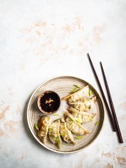 Tradycyjne chińskie pierożki - gyoza z wieprzowiną i warzywami na okrągłym talerzu z sosem sojowym w misce.