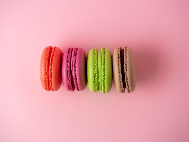 Tradycyjne ciasteczka makaroniki w różnych kolorach leżą na różowym tle.