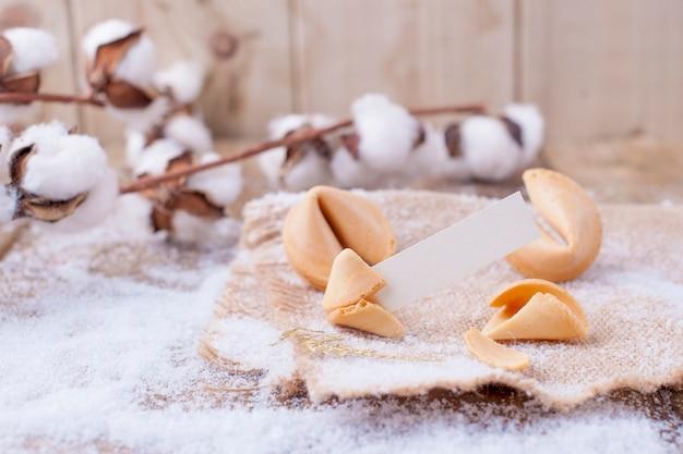 Tradycyjne ciasteczka z życzeniami na boże narodzenie i nowy rok, na drewnianym stole i gałęzi z bawełną