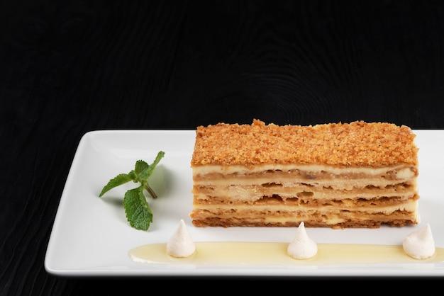 Tradycyjne ciasto esterhazy z miętą na czarnym drewnianym tle