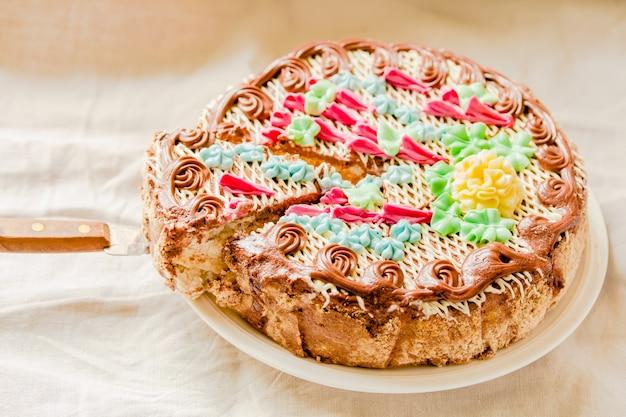 Tradycyjne ciasto kijów (kijów) lub beza daquoise kawałek ciasta z kremem maślanym na talerzu. smaczne ciasto na wakacje na białym tle lnianym komfortu. wolne miejsce na tekst.