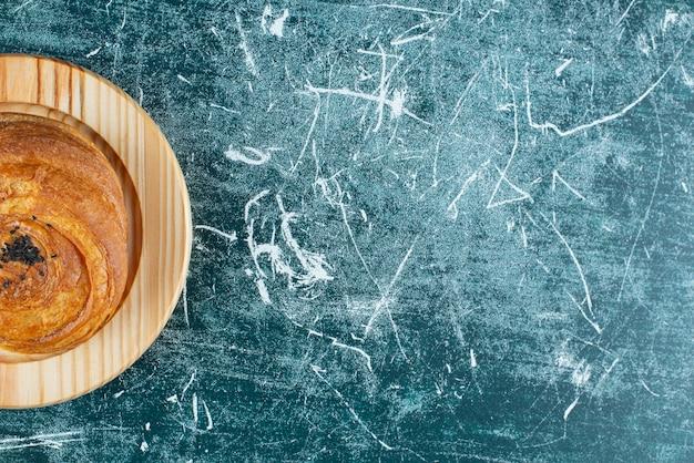 Tradycyjne ciasto ozdobione sezamem na drewnianym talerzu.