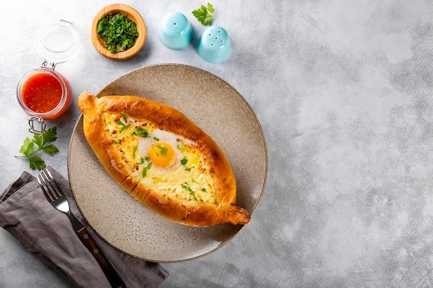 Tradycyjne danie kuchni gruzińskiej adjarian chaczapuri z serem, jajkiem i pikantnym pomidorem