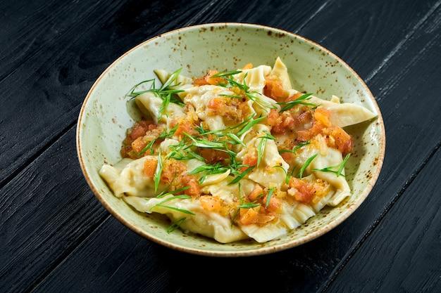 Tradycyjne danie kuchni izraelskiej - kurczak kreplach z salsą pomidorową i zieloną cebulą w talerzu na czarnym tle drewnianych. jedzenie w restauracji. pierogi z różnymi nadzieniami