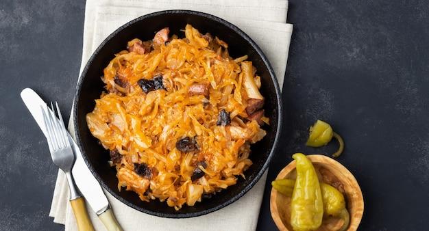 Tradycyjne danie kuchni polskiej - bigos ze świeżej kapusty, mięsa i suszonych śliwek. widok z góry. ciemne tło.