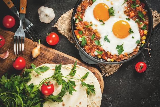 Tradycyjne danie meksykańskie huevos rancheros - jajecznica z salsą pomidorową, tortille taco, świeże warzywa i natka pietruszki. śniadanie dla dwojga. na czarnym betonowym stole. widok z góry, kopia przestrzeń