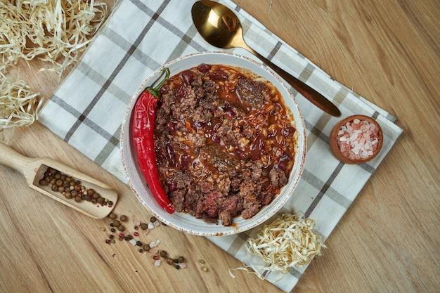 Tradycyjne danie meksykańskie to zupa chili con carne z duszoną wołowiną w kompozycji z przyprawami na drewnianym stole. smaczne jedzenie