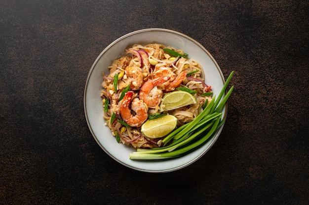 Tradycyjne danie pad thai z krewetkami na ciemnym tle, widok z góry