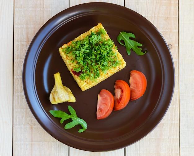 Tradycyjne danie środkowoazjatyckie - pilaw (plov risotto) w formie kwadratu, ozdobione posiekaną natką pietruszki w glinianej misce na lekkim drewnianym stole. widok z góry