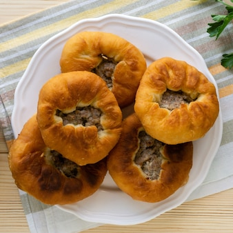 Tradycyjne danie tatarskie i baszkirskie belyashi. otwarte smażone placki z mięsem mielonym i cebulą.