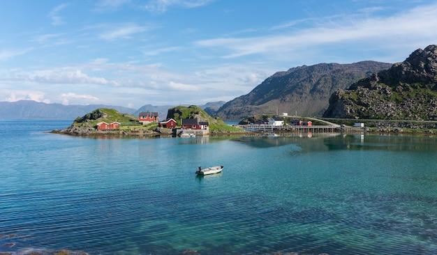 Tradycyjne domki rybaków i łódź w morskiej zatoce, finnmark, norwegia
