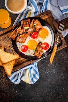 Tradycyjne domowe angielskie śniadanie amerykańskie, jajka sadzone, grzanki, bekon z kubkiem kawy i sokiem pomarańczowym