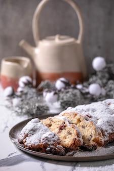 Tradycyjne, domowe, niemieckie boże narodzenie pieczenia chleba stollen ciasto na talerzu ze srebrnymi dekoracjami świątecznymi na białym tle marmuru