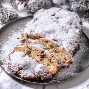 Tradycyjne domowe niemieckie boże narodzenie pieczenia chleba stollen ciasto na talerzu ze srebrnymi dekoracjami świątecznymi na białym tle marmuru.