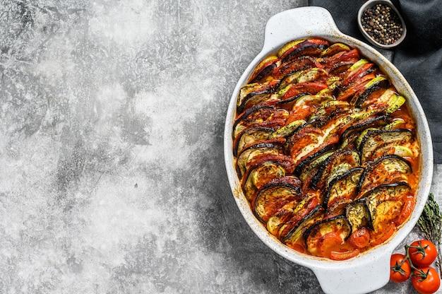 Tradycyjne domowe ratatouille warzywne pieczone w naczyniu. szare tło.