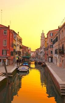 Tradycyjne domy w wenecji nad wodą małego kanału na starym mieście o zachodzie słońca, włochy