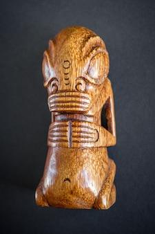 Tradycyjne drewniane tiki polinezyjskie z markizów. na białym tle na ciemnym tle