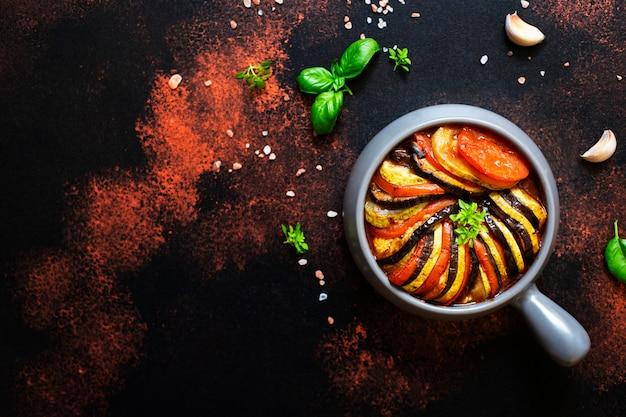 Tradycyjne francuskie danie ratatouille z pieczonych letnich warzyw podawane na blasze. żywność wegetariańska i dietetyczna. kuchnia francuska / jedzenie. ciemne tło rustykalne, widok z góry, miejsce