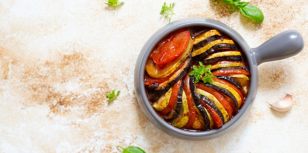 Tradycyjne francuskie danie ratatouille z pieczonych letnich warzyw podawane na blasze. żywność wegetariańska i dietetyczna. kuchnia francuska / jedzenie. marmurowy lekki tło, odgórny widok, kopii przestrzeń