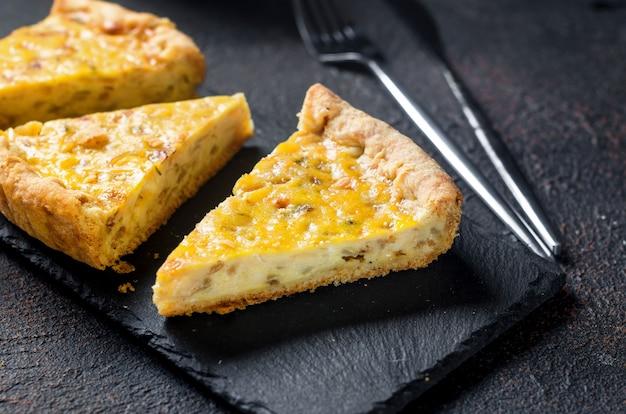 Tradycyjne francuskie domowe ciasto cebulowe lub quiche. otwórz ciasto z serem i cebulą na okrągłej desce na ciemnym stole.