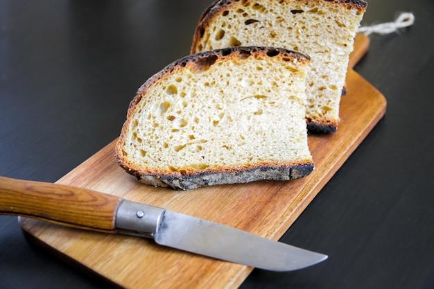 Tradycyjne francuskie kraj chleb kromki i scyzoryk na drewnianej desce do krojenia.
