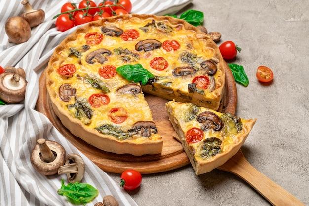 Tradycyjne francuskie pieczone domowe ciasto quiche na drewnianej desce do krojenia
