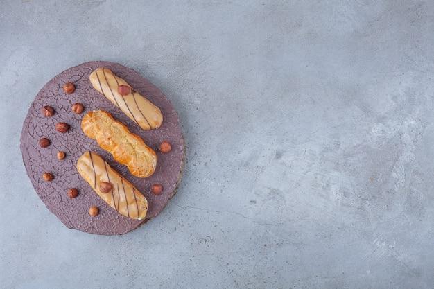 Tradycyjne gładkie eklery z orzechami laskowymi umieszczonymi na drewnianym kawałku.