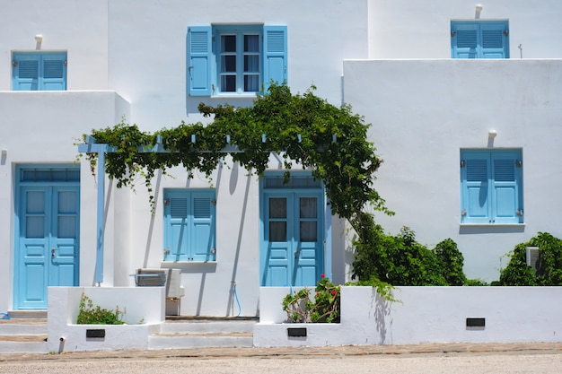Tradycyjne greckie domy architektoniczne pomalowane na biało z niebieskimi drzwiami i okiennicami