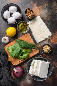 Tradycyjne greckie składniki spanakopita filo szpinak jaja feta widok z góry na ciemnym tle.