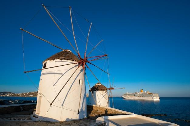 Tradycyjne greckie wiatraki na wyspie mykonos o wschodzie słońca, cyklady, grecja