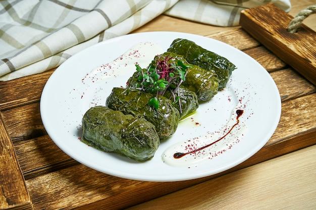Tradycyjne gruzińskie dolma w liściach winogron obsadzonych ryżem i mięsem na białym talerzu na drewnianym stole. ścieśniać. .