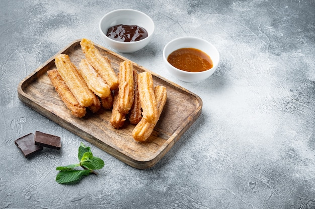 Tradycyjne hiszpańskie churros deserowe z zestawem cukru i czekolady, na szarym tle z miejscem na tekst, copyspace