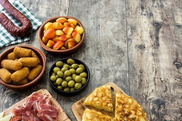 Tradycyjne hiszpańskie tapas. krokiety, oliwki, omlet, szynka i patatas bravas na drewnianym stole kopiować miejsca