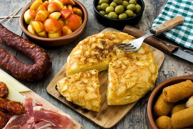 Tradycyjne hiszpańskie tapas. krokiety, oliwki, omlet, szynka i patatas bravas na drewnianym stole