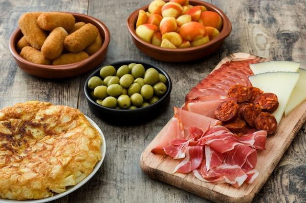 Tradycyjne hiszpańskie tapas krokiety, oliwki, omlet, szynka i patatas bravas na drewnianym stole