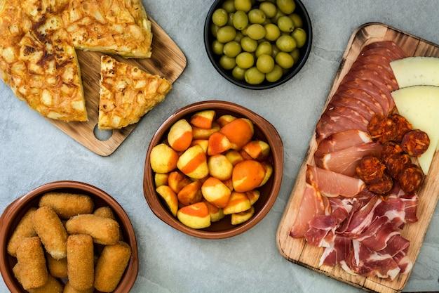 Tradycyjne hiszpańskie tapas krokiety, oliwki, omlet, szynka i patatas bravas na szarym kamieniu