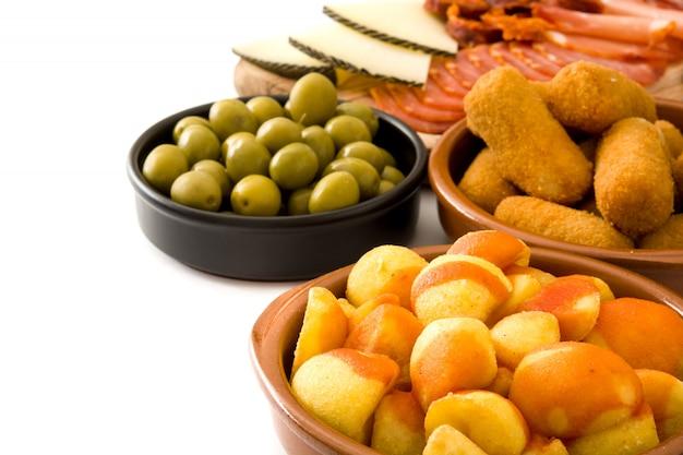 Tradycyjne hiszpańskie tapas z krokietami, oliwkami, szynką i patatas bravas na białym tle