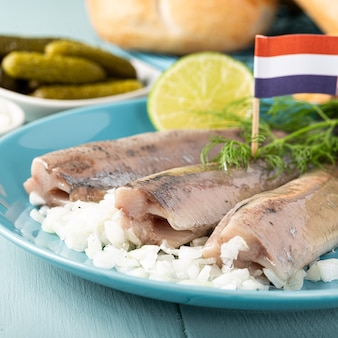 Tradycyjne holenderskie jedzenie świeżo solony śledź z cebulą hollandse nieuwe na turkusowym talerzu i drewnianej powierzchni. europejska koncepcja żywności